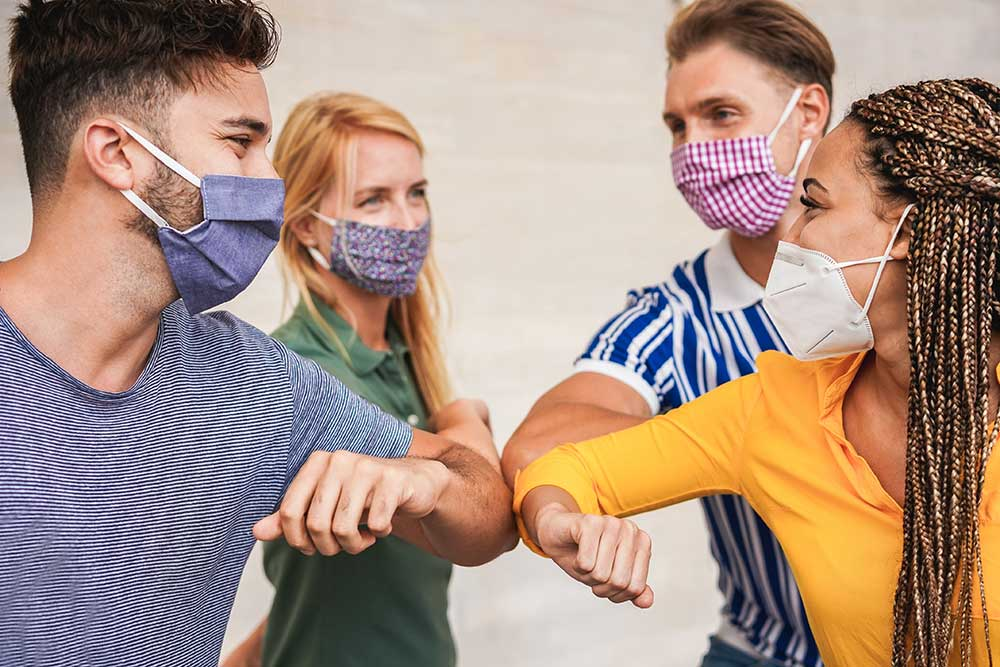 Teens wearing cloth face masks touch elbows, rather than high-five or handshake